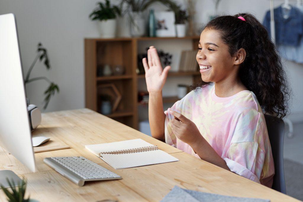 Mädchen winkt in Webcam